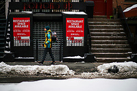 NEW YORK, NEW YORK - FEBRUARY 4:  A man walks at hells kitchen district where some restaurants remain closed on February 12, 2021 in New York. New York City is getting back their indoor dining with a restriction of 25 percent capacity. most of the restaurants have set up outdoor dining structures like pods, bubbles and lot of makeshift cabins. (Photo by Eduardo MunozAlvarez/VIEWpress)