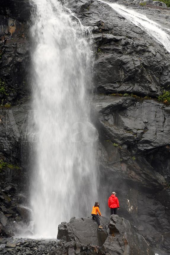 Hikers at waterfalls below Cataract Glacier, Harriman Fiord, Prince William Sound, Chugach National Forest, Alaska.