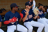 Elizabethton Twins Colton Burns (23) poses for a photo with Yunior Severino (22) next to Ricky De La Torre (7) in the dugout before a game against the Bristol Pirates on July 28, 2018 at Joe O'Brien Field in Elizabethton, Tennessee.  Elizabethton defeated Bristol 5-0.  (Mike Janes/Four Seam Images)