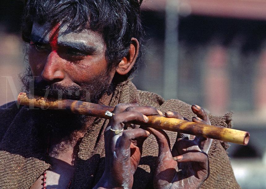 A SHAIVITE SADHU or Hindu follower of Shiva plays flute at the Hindu Temple complex of PASHUPATINATH,  KATHAMANDU, NEPAL