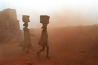 Two children carry bricks on their heads through the fume-filled air at a brick factory.  Brick factories are a major source of deadly fumes and cause chronic respiratory problems in children who work there.
