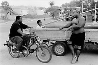 Republic of Nauru. Central Pacific. Nauru is a tiny island (21 square-km). A fat man is seated on his bike and talks to another big man lying on the back of a truck near the unique concrete road around the island. © 1999 Didier Ruef
