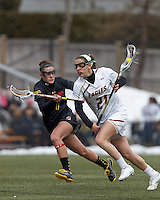 Boston College midfielder Caroline Margolis (21) on the attack as University of Maryland midfielder Katie Schwarzmann (7) defends..University of Maryland (black) defeated Boston College (white), 13-5, on the Newton Campus Lacrosse Field at Boston College, on March 16, 2013.