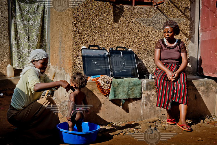 In the district of Kisalosalo, district of Kyebando, in the suburbs of Kampala, Mastulah Nakisozi sits next to a Solvatten solar water purifier that she has placed in the sun while she watches her neighbour wash her daughter. Nakisozi is part of a group of people infected with HIV who joined together to buy the purifier, with the help of an NGO, so they would have access to clean drinking water.