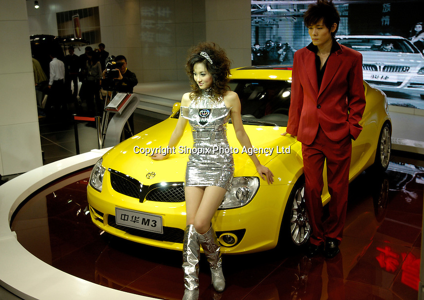 Chinese models perform beside a Brilliance M3 coupe of Brilliance Auto at the 2006 International Automotive Exhibition in Beijing, China..