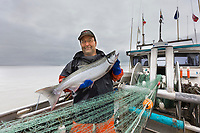 Commercial fisherman Bill Webber shows a red salmon caught in his drift gill net during an opener on the Copper River delta flats, near Cordova, Alaska.
