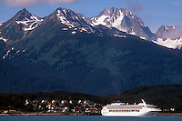 A cruise ship sits in front of Haines, Alaska, with the Takninsha mountain range in the background.
