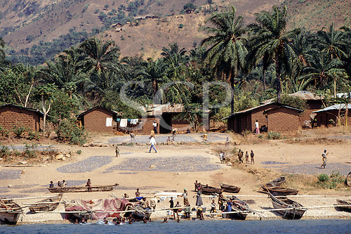 Tanzania, Africa. Village on the shores of Lake Tanganyika with dagaa fish drying in the sun and fishing boats on the beach and children.