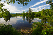 Reflection of trees and clouds in Coffin Pond in Sugar Hill, New Hampshire USA during the spring months.