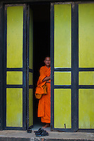 Monk in a colorful doorway at a Monastery in Battambang, Cambodia