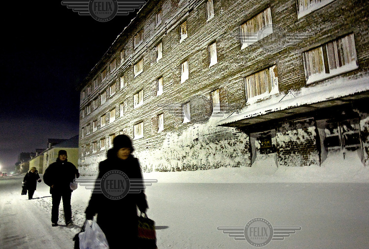 People walk by an empty boarding house. Vortuka's population has fallen by a third since the break-up of the Soviet Union, when subsidies for Russia's far north were reduced. Vorkuta is a coal mining and former Gulag town established beyond the Arctic Circle, where temperatures in winter drop to -50C. Russia's far north is slowly declining. Every year thousands of people from its towns and cities flee south. The system of subsidies that propped up Siberia and the Arctic in Soviet times has crumbled. Now there is no advantage to living in the far north, salaries are no higher than in central Russia and prices for goods are higher. /Felix Features