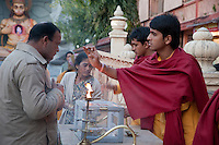 India, Rishikesh.  Monk Giving Blessing to Worshipper after Evening Prayer (Aarti) at the Parmarth Niketan Ashram.  Hanuman Shrine in Background.