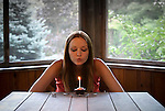 Young woman seated at a table blowing out a candle on a cupcake