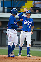 Ben Johnson (6) of the Burlington Royals high fives teammates Meibrys Viloria (4) after they both scored runs against the Danville Braves at Burlington Athletic Park on July 12, 2015 in Burlington, North Carolina.  The Royals defeated the Braves 9-3. (Brian Westerholt/Four Seam Images)