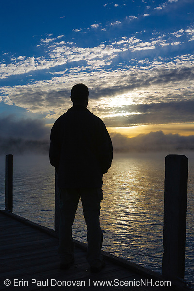 Wellington State Park - The silhouette of a man on dock watching sunrise over Newfound Lake in Bristol, New Hampshire USA.