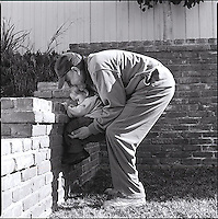 Father teaching child beginning rock climbing<br />