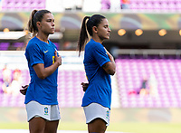 ORLANDO, FL - FEBRUARY 24: Tamires #6 and Debinha #9 of Brazil stands during their national anthem before a game between Brazil and Canada at Exploria Stadium on February 24, 2021 in Orlando, Florida.