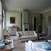 An 18th century tiled stove and a portrait of Gustav III take centre stage in the sitting room