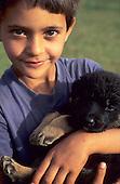 Bahia, Brazil. Boy holding a puppy.