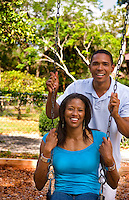 Black African American couple dating and playing on swing at playground