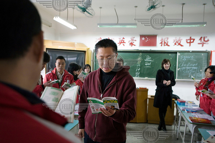 """Li Yang visits individual 'Crazy English' classes to give students some personal tuition on their English. Students range from young school children to adults. Each class has an English speaking foreigner assisting the class teacher. To his fans, Li is less a language teacher than a testament to the promise of self-transformation. In the two decades since he began teaching, at age nineteen, he has appeared before millions of Chinese adults and children. He routinely teaches in arenas to classes of twenty thousand people. Some fans travel for days to see him. The most ardent students opts for a """"diamond degree"""" ticket, which includes bonus small group sessions with Li. The list price for those seats is 250 USD a day - about a full month's wages for the average Chinese worker."""