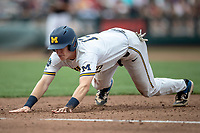Michigan Wolverines first baseman Jimmy Kerr (15) dives back to first base during Game 1 of the NCAA College World Series against the Texas Tech Red Raiders on June 15, 2019 at TD Ameritrade Park in Omaha, Nebraska. Michigan defeated Texas Tech 5-3. (Andrew Woolley/Four Seam Images)