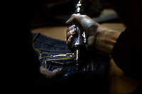 """A textile worker drills holes in a pair of jeans at a garment factory. The factory, which specifically carries out a wear-and-tear process used to achieve a fashionable distressed look, produces approximately 10,000 pairs of jeans every day. Thousands of workers labour through the night scrubbing, spraying and tearing jeans in order to meet the production demand. The factory is owned by Huang Dehong, who left his impoverished village and arrived penniless in Zhongshan twenty years ago. China, the """"factory of the world"""", is now one of the world's largest producers of jeans and its textile workers are among the 200 million migrant labourers criss-crossing the country looking for a better life."""