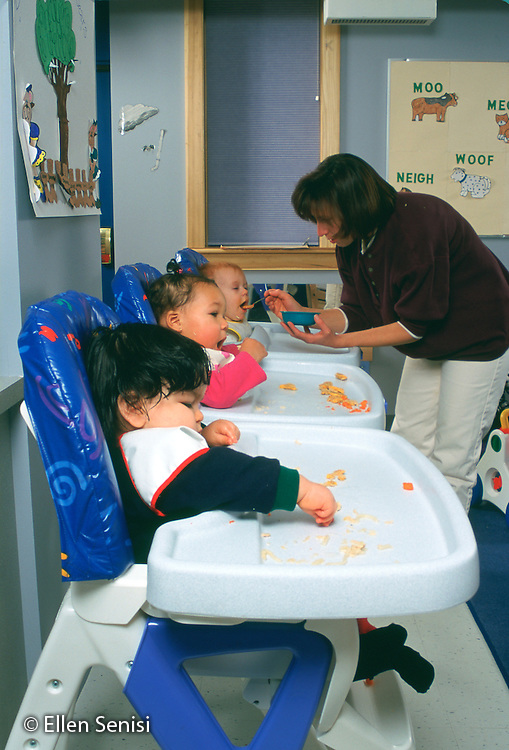 MR / Schenectady, NY.Schenectady Day Nursery / private non-profit daycare center / Infant Class.Babies feed themselves carrots at lunchtime; aide helps. (left to right: boy, 12 months / girl: 12 months / Girl: 7  months).MR: Vro1, Kin7, Bru2, Ada4.PN#: 25128                                         FC#: 21805-00314.scan from slide.©Ellen B. Senisi