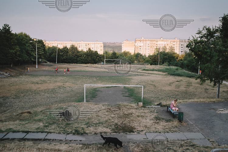 A woman sits beside a football pitch, where a group of children and dogs are playing, in the Ciocana district.