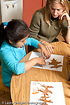 Education preschool 3-4 year olds female student teacher working with girl on nature art activity gluing fall leaves to paper vertical