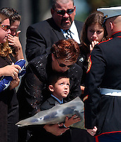 X.memorial.1.0830.jl.jpg/photo jamie scott lytle/Held by his mother Lori Moreno, Matthew Parkerson, age 6, looks up at a Marine Honor Guard after receiving an American flag at his fathers Marine Sgt. Harvey Emmett Parkerson III, memorial service held at Ft. Rosecrans National Cemetary Monday. Parkerson was killed in action August 18th in Najaf Iraq.