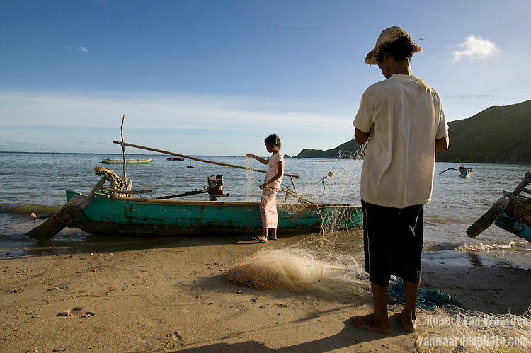 Fisherman prepare their nets for an evening of fishing in Kuta, Lombok, Indonesia