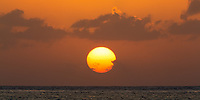 Beautiful Caribbean Sea sunset on Cozumel Island, with the sun as an enormous yellow ball in a colorful, orange sky, Yucatan Peninsula, Mexico