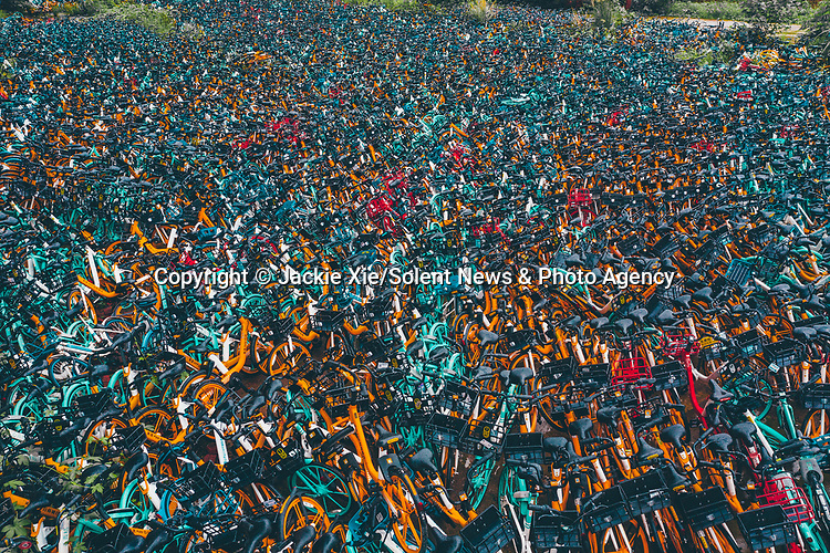 Pictured: This bicycle 'graveyard' is full of thousands of broken bikes waiting to be be repaired or destroyed.   They all belong to bike rental companies and have been stacked on top of each other in the Chinese city of Chengdu as they await their fate.<br /> <br /> Before being dumped they had all been cheap to rent by scanning a code with a mobile phone to unlock them.   Photographer Jackie Xie, who captured the scene, said the lack of care people gave them seemed typical of the way people treat many things in life these days.   SEE OUR COPY FOR DETAILS<br /> <br /> Please byline: Jackie Xie/Solent News<br /> <br /> © Jackie Xie/Solent News & Photo Agency<br /> UK +44 (0) 2380 458800