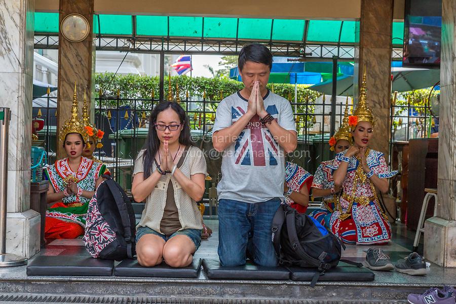 Bangkok, Thailand.  Erawan Shrine.  Donors Pray While Dancers Perform Dance as a Blessing.