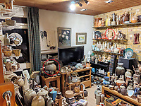 BNPS.co.uk (01202 558833)<br /> Pic: AdamPartridgeAuctioneers/BNPS<br /> <br /> Pictured: The Shurz's living room at the house in Digswell includes a wood fired stoneware vase by Ken Matsuzaki (circled left) and a wedding vase by Gloria Kahn (circled right) with painted decoration. <br /> <br /> A huge collection of pottery and ceramics found stacked inside the suburban home of an elderly couple has sold for almost £200,000.<br /> <br /> Leonard and Alison Shurz filled every room of their three bed house with ceramic pieces they had gathered from all over the world.<br /> <br /> The Aladdin's Cave of pots, bowls, plates, vases and jugs was found by a stunned auctioneer who had the daunting task of cataloguing it all.