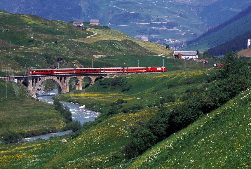 train, Switzerland, Uri, Urseren, Alps, The red Glacier Express Train travels through the scenic valley near the village of Hospental in the Swiss Alps.