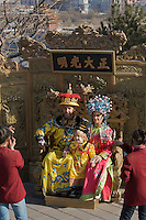 Foreign tourists pose for pictures with a Chinese staff, both dressed in Qing dynasty imperial costume, in the Jingshan Park, Beijing, China..27 Feb 2008