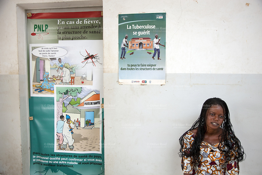 Senegal. Thies region. Mekhe. Hospital ( District sanitaire). A woman suffering from fewer waits for a medical consultation. On the wall, two posters. The first (L) recommends the use of mosquitoes impregnated bednets used in tackle malaria prevention program' awareness with its visual impact. The campaign is ran by the Conseil National de lutte contre le paludisme (PNLP). The second (C) confirms that tuberculosis (TB) can be cured when properly treated. The campaign is ran by the Ministry of Health and Medical Prevention. The Global Fund supports with financial grants both principal recipients, the Ministry of Health for TB and the PNLP program. 04.12.09 © 2009 Didier Ruef  / The Global Fund