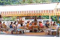 Seaside Restaurant outside seating terrace. Guests sitting eating and drinking in the shade, a waiter taking orders. Hotel and restaurant Kompas. Uvala Sumartin bay between Babin Kuk and Lapad peninsulas. Dubrovnik, new city. Dalmatian Coast, Croatia, Europe.