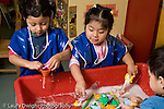 Educaton preschool  3-4 year olds two girls and a boy playing at water table horizontal