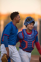 AZL Cubs 2 starting pitcher Yovanny Cruz (58) and catcher Henderson Perez (8) walk off the field between innings of an Arizona League game against the AZL Reds at Sloan Park on June 18, 2018 in Mesa, Arizona. AZL Cubs 2 defeated the AZL Reds 4-3. (Zachary Lucy/Four Seam Images)