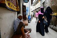 TANZANIA Zanzibar, Stone town is part of UNESCO heritage, veiled muslim women and sleeping man / TANSANIA Insel Sansibar, Stonetown, die Altstadt ist Teil des Unesco Welterbe Programm, 99 Prozent der Bewohner sind Muslime