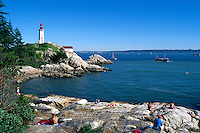 Point Atkinson Lighthouse (built 1912) in Lighthouse Park, West Vancouver, BC, British Columbia, Canada - People sunbathing on Rocks overlooking English Bay and Howe Sound
