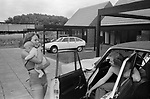 1970s UK, professional middle income couple outside their new modern home on a recently built new housing development. Hanging out with the new baby in arms by their car that is parked out side their home 1977 England. Milton Keynes Buckinghamshire.