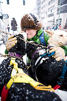 Gwenn Perkins, handler for Michelle Phillips of Canada, gives the dogs one last hug before they set off on the Matt Failor, of the 2012 Iditarod Ceremonial Start, Anchorage, AK.
