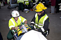 Paramedic ambulance crew and firefighters attending a road traffic accident involving a car stolen by a joyrder that was then involved in a head on crash. She has been extricated from the vehicle and has been placed on a spinal board and has had a total neck brace attached.