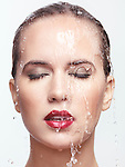 Closeup beauty portrait of a woman face with red lipstick and makeup with water running over it. Isolated on white background. Image © MaximImages, License at https://www.maximimages.com