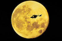 Silhouette of a helicopter flying at night in front of a full moon.