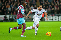 Ashley Williams of Swansea moves the ball forwards past Enner Valencia of West Ham United during the Barclays Premier League match between Swansea City and West Ham United played at the Liberty Stadium, Swansea  on December 20th 2015